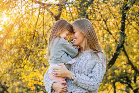 Photo pour Portrait of loving beautiful woman holding her little girl in hands and smiling while standing outdoors. Young mother and her daughter hugging each other in autumn park. Happy lovely family concept - image libre de droit