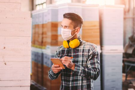 Foto de Portrait of man supervisor in medical face mask and protective headphones checking wood material inventory at storage. Young warehouse worker inspecting, counting woodwork stock. COVID-19 quarantine - Imagen libre de derechos