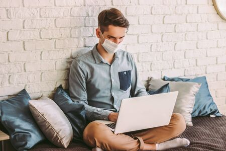 Photo for Busy hipster man in medical face mask surf internet on laptop, sit on couch at cozy home workplace. Businessman in protective mask use computer for distance work from home office. COVID-19 quarantine - Royalty Free Image