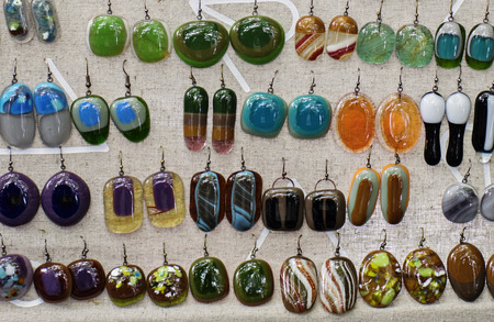 Photo pour Display with artisan jewelry, fused glass dangling earrings, wide array of styles and colors - image libre de droit