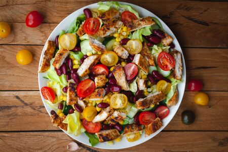 Photo pour Close-up of chicken salad with fresh vegetables in a plate, on wooden background, top view - image libre de droit