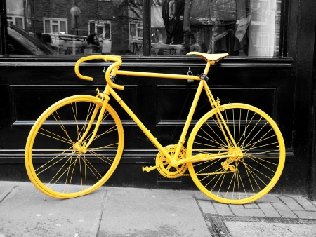 b&w photo of old yellow bike on the window of the coffe shop