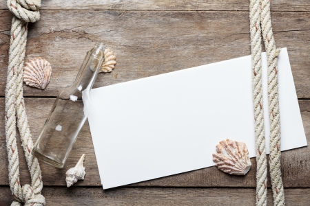 Blank paper sheet on weathered wood background with rope, shells, and bottle