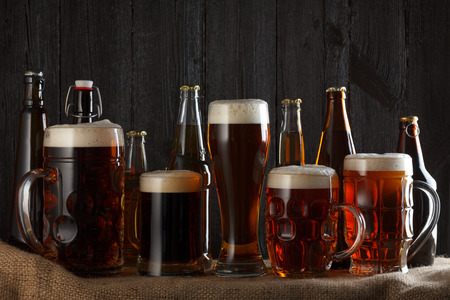Beer glasses and bottles with lager, dark lager, brown ale, malt and stout beer on table, dark wooden background