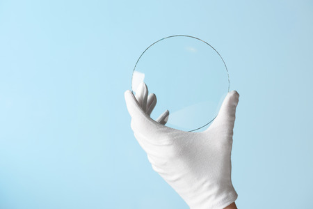 Scientist hand in glove show circle piece of new research prototype of transparent clear glass or plastic material