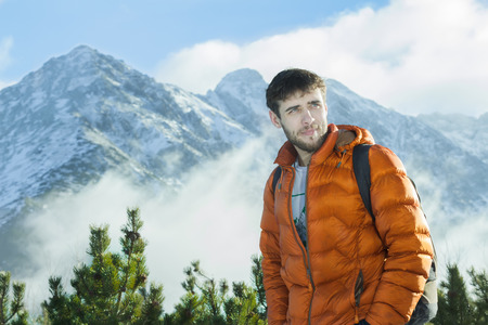 Handsome mountaineer is posing at astonishing snowy rocky landscape background