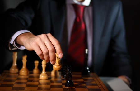 Photo for Image of a businessman in dark suit playing chess - Royalty Free Image