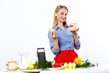Young happy woman cooking fresh meal at home