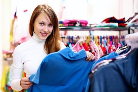 Photo pour Portrait of young woman inside a store buying clothes - image libre de droit