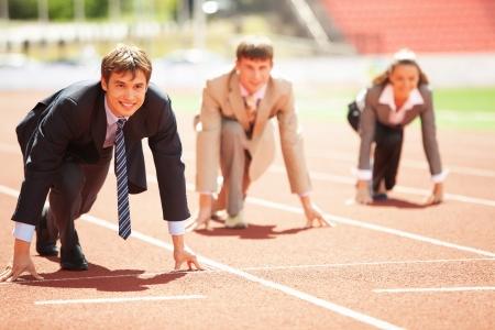 Businessmen running on track racing at athletich stadium