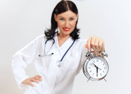 Portrait of happy successful young female doctor holding clocks