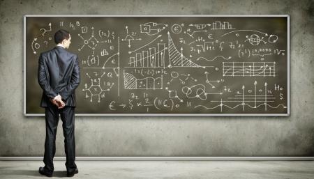Foto de Business person standing against the blackboard with a lot of data written on it - Imagen libre de derechos