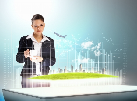 Image of young businesswoman holding cup standing against high-tech picture