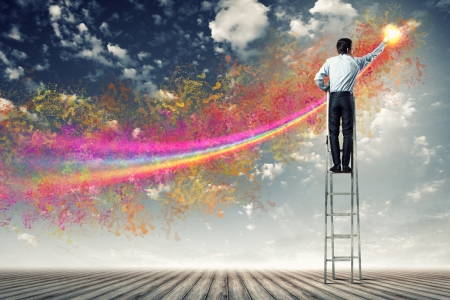 young man standing with back on ladder painting splashes