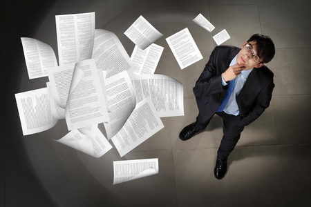 Image of printed materials flying in air top view against businessman background