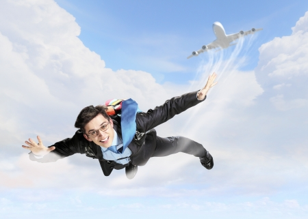 Photo pour Conceptual image of young businessman flying with parachute on back - image libre de droit