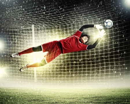 Goalkeeper catches the ball   At the stadium, in the spotlight