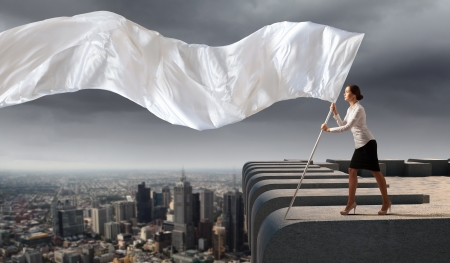 Image of attractive businesswoman holding white flag  Place for text