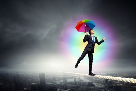 Businessman in black suit with umbrella balancing on rope