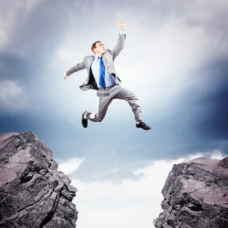 Photo pour Image of young businessman jumping over gap - image libre de droit