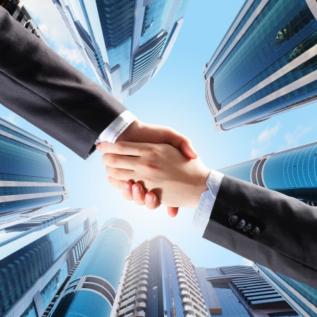 Close up image of hand shake against skyscrapersの写真素材
