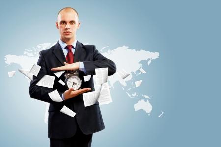 Image of businessman holding alarmclock against illustration background  Collage