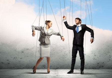 Image of businesspeople hanging on strings like marionettes  Conceptual photography