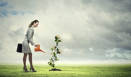 Image of business woman watering money tree  Currency concept