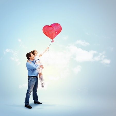 Image of happy father holding his daughter and a red heart baloon