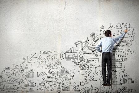 Back view of businessman drawing sketch on wall