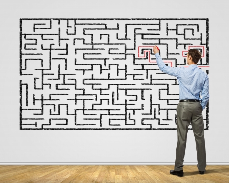 Photo for Back view image of young businessman trying to find way out of maze - Royalty Free Image