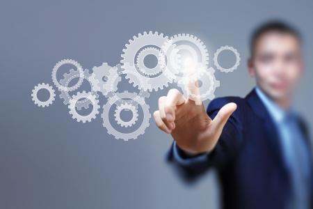 Foto de Image of businessman touching gear elements  Mechanism concept - Imagen libre de derechos
