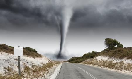 Image of powerful huge tornado twisting on road