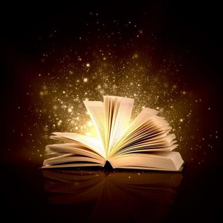 Foto de Image of opened magic book with magic lights - Imagen libre de derechos