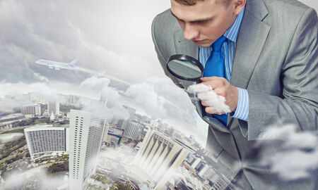Image of businessman examining objects with magnifier