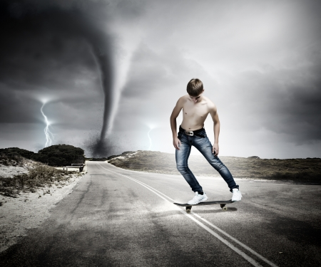 Skater in jeans on road with tornado at background