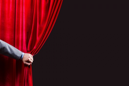 Close up of hand opening red curtain  Place for text