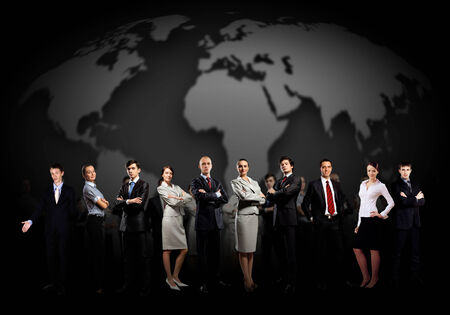 Group of business people standing together against a world map
