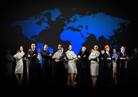 Group of businesspeople standing together against a world map
