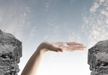 Close up of human hand between mountain gap