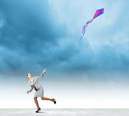 Photo pour Young happy businesswoman running with colorful kite - image libre de droit