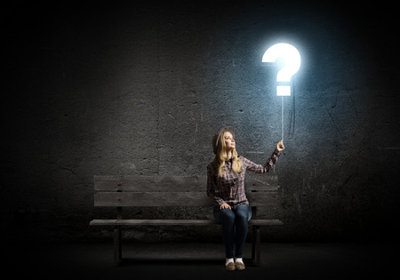 Young woman in casual holding balloon shaped like question mark