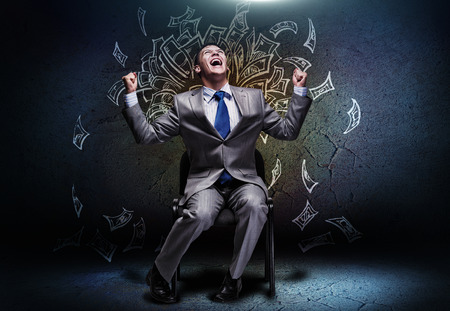 Photo pour Joyful businessman sitting on chair under money rain - image libre de droit