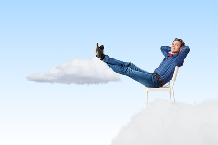 Photo pour Young man sitting in chair with legs up and relaxing - image libre de droit