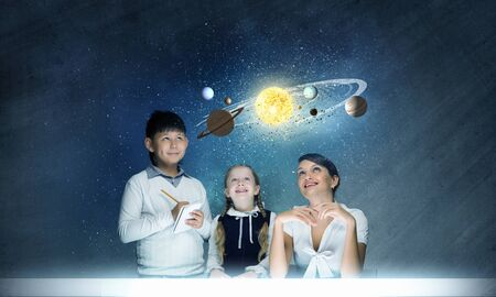 Teacher and two pupils at astronomy lesson exploring space