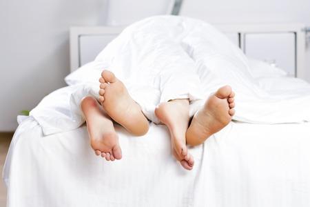 Photo pour Close up of four feet in a bed - image libre de droit