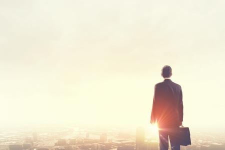 Foto de Rear view of businessman looking at sunset above city - Imagen libre de derechos