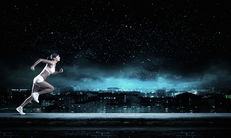 Young woman athlete running fast on dark background
