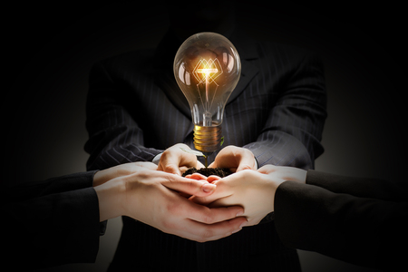 Photo pour Brainstorming and teamwork concept with diverse business people holding light bulb in hands - image libre de droit