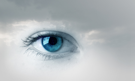 Photo pour Female blue eye on cloudy sky background - image libre de droit